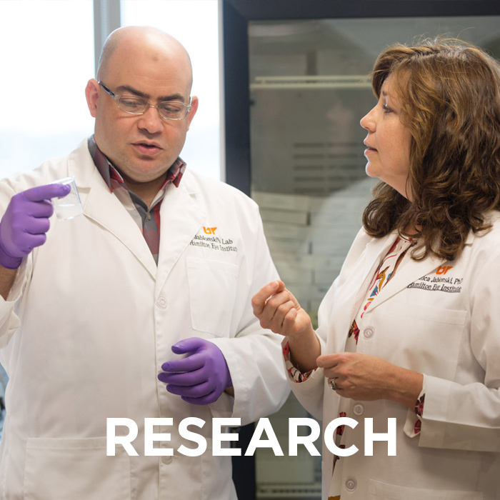 "Researchers discussing in a lab. The word ""research"" appears over the image. Click this image to view pages on research at Hamilton Eye."