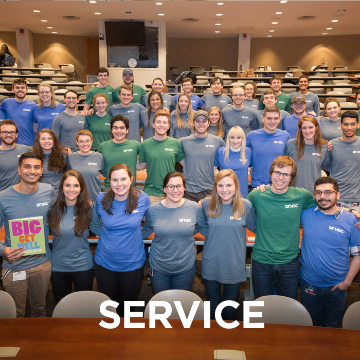 "Large group of students pose for photo while wearing shirts from a service project. The word ""service"" is imposed on the lower part of the photo."
