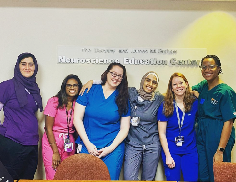 Six female residents in the hallways of the Neuroscience Education Center