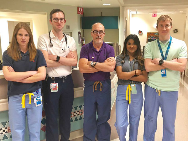 Four residents with Dr. Bugnitz in the hospital hallway